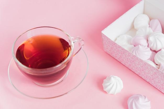 Białe I Różowe Kręcone Bezy I Filiżankę Herbaty Na Różowym Tle Premium Zdjęcia