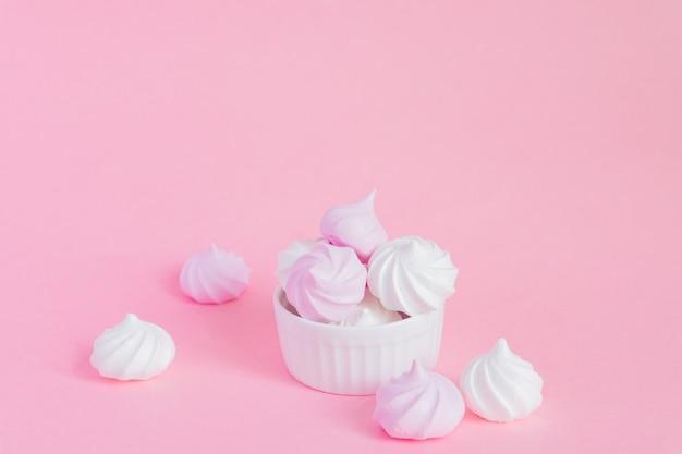 Białe I Różowe Kręcone Bezy W Porcelanowym Pucharze Na Różowym Tle, Kartka Z Pozdrowieniami, Kopii Przestrzeń Premium Zdjęcia
