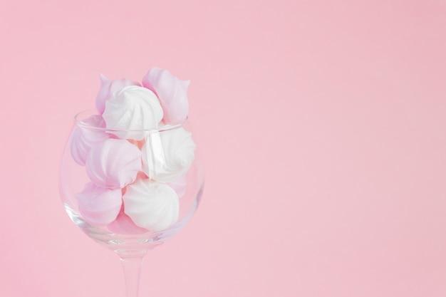 Białe I Różowe Skręcone Bezy W Kieliszku Winorośli Na Różowym Tle Premium Zdjęcia