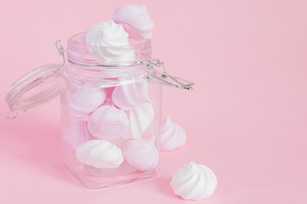 Białe I Różowe Skręcone Bezy W Szklanym Słoju Na Różowym Tle Premium Zdjęcia