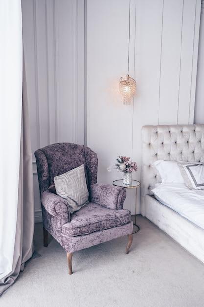 Białe Klasyczne Wnętrze Sypialni Z świątecznym Bukietem W Wazonie, Delikatnie Różowym Pudełkiem Prezentowym Na Szklanym Stoliku Przy łóżku I Klasycznym Fotelem W Lawendowych Kolorach Premium Zdjęcia