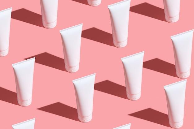 Białe Kremowe Tubki Na Jasnoróżowym Stole. Dbaj O Skórę Twarzy, Dłoni, Nóg I Skóry. Premium Zdjęcia