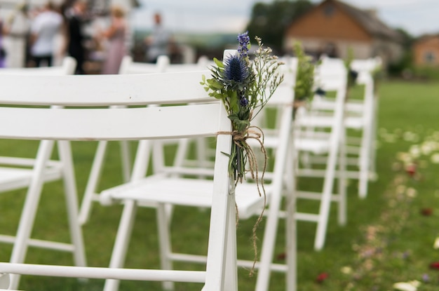 Białe Krzesła Weselne Ozdobione świeżymi Kwiatami Na Zielonej Trawie. Puste Drewniane Krzesła Dla Gości Na Zielonym Trawniku W Ogrodzie Przygotowane Na ślub. Premium Zdjęcia