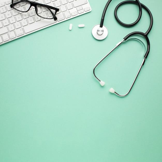 Białe pigułki i stetoskop w pobliżu okularów na bezprzewodowej klawiaturze na tle Darmowe Zdjęcia