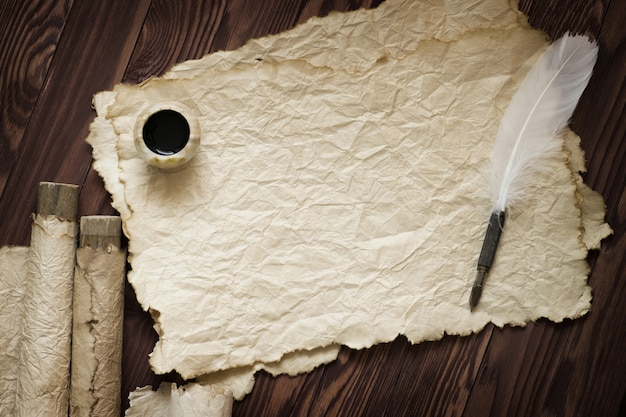 Białe piórko i starożytny zwój na brązowej desce Premium Zdjęcia