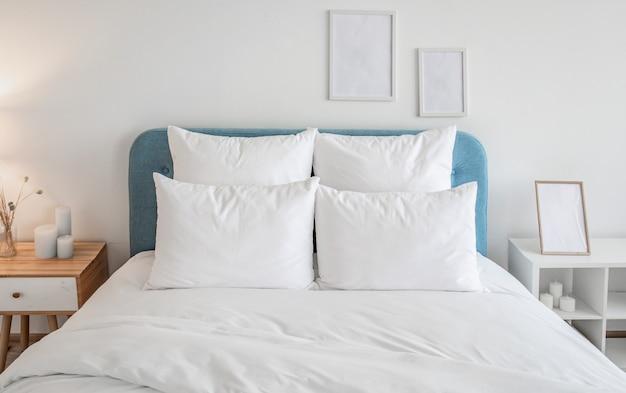 Białe poduszki i kołdra na niebieskim łóżku. Premium Zdjęcia