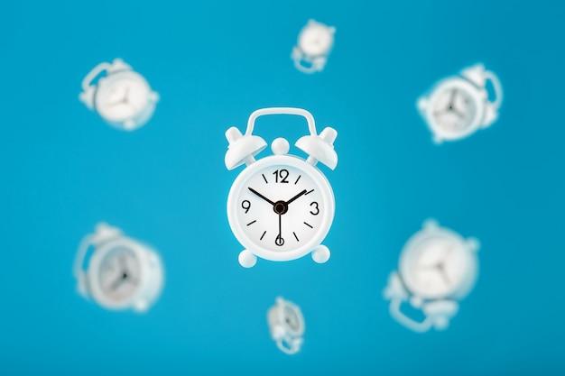 Białe Retro Budziki W Locie W Centrum, Na Białym Tle Na Niebieskim Tle. Kreatywnych Nowoczesny Martwa Koncepcja Latania Czasu. Premium Zdjęcia