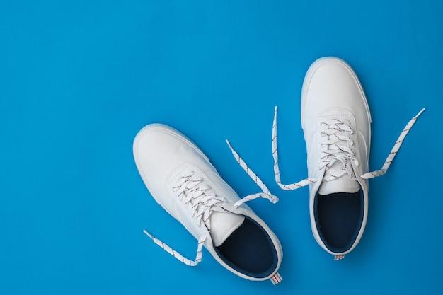 Białe Tenisówki Z Rozwiązanymi Sznurówkami Na Niebieskiej Powierzchni Premium Zdjęcia