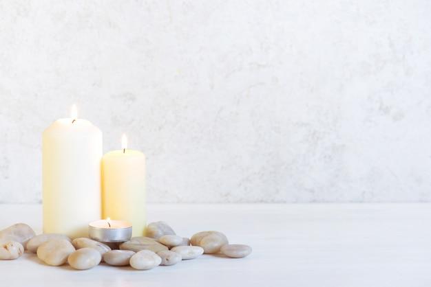Białe tło z trzema płonącymi świecami i kamieniami Premium Zdjęcia