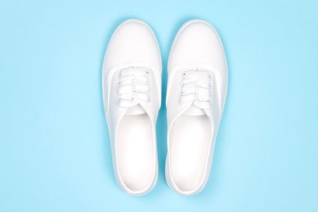Białe trampki na niebieskim tle, płaskie, modne buty, Premium Zdjęcia