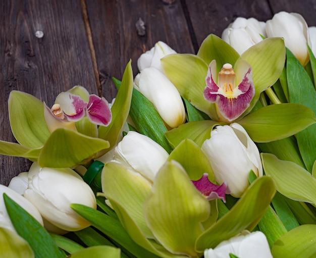 Białe Tulipany I Zielone Orchidee Na Ciemnym Drewnianym Stole Premium Zdjęcia