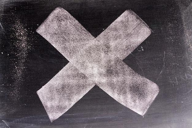 Białego koloru chak ręki rysunek w krzyżu lub x kształt na blackboard tle Premium Zdjęcia