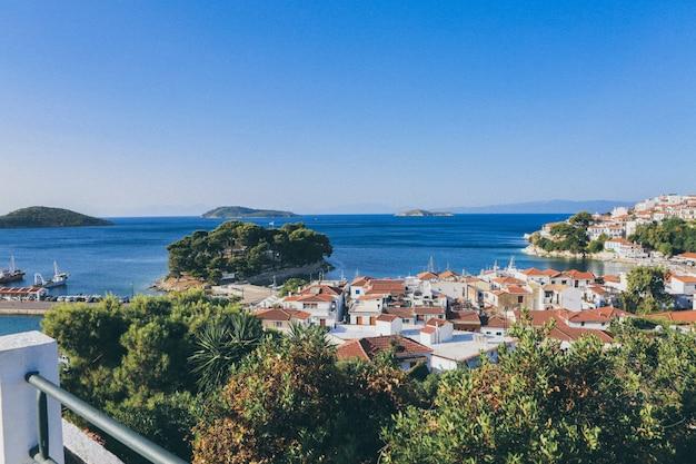Biali I Brown Budynki Zbliżają Morze Otaczającego Drzewami I Małymi Wyspami W Skiathos, Grecja Darmowe Zdjęcia