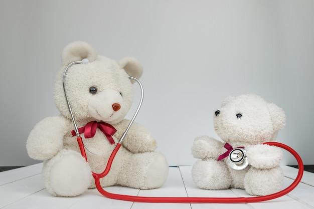 Biali lalek niedźwiedzie z doktorskim instrumentu stetoskopem na bielu. Premium Zdjęcia