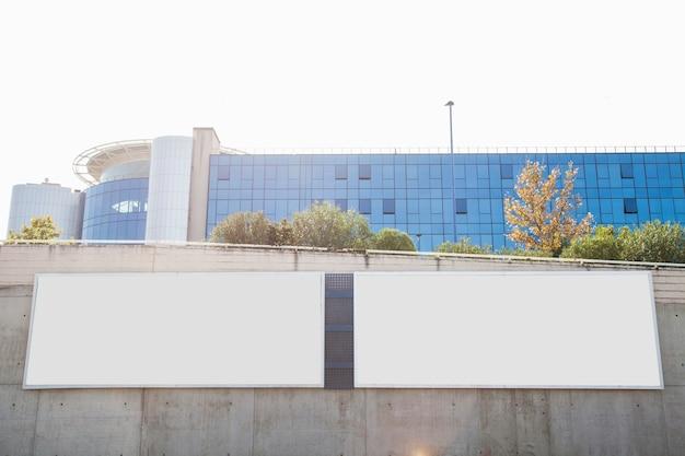 Biali puści billboardy na betonowej ścianie przed korporacyjnym budynkiem Darmowe Zdjęcia