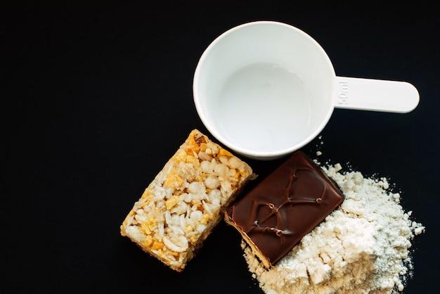 Białka w proszku i batony energetyczne na czarnej ścianie Premium Zdjęcia