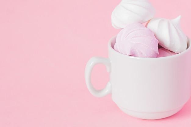 Biało-różowe Bezy Skręcone W Małej Porcelanowej Filiżance Kawy Na Różowym Tle Premium Zdjęcia