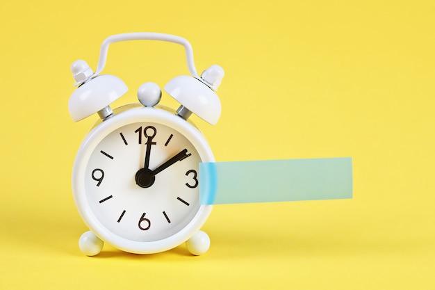 Biały budzik. pusta karteczka na zegarze. kopia miejsca. minimalna koncepcja. Premium Zdjęcia