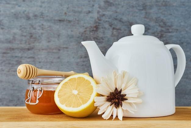 Biały ceramiczny czajniczek, miód lemonnd w szklanym słoju z bliska Premium Zdjęcia