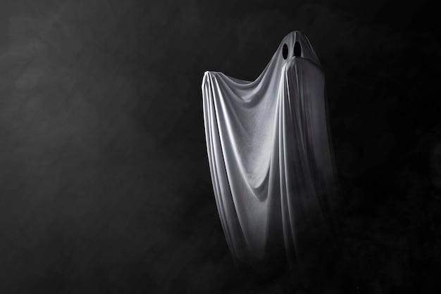 Biały Duch Nawiedzający Na Ciemnym Tle. Koncepcja Halloween Premium Zdjęcia