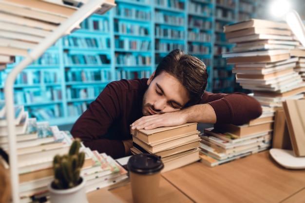Biały Facet Otoczony Książkami W Bibliotece. Student śpi Premium Zdjęcia