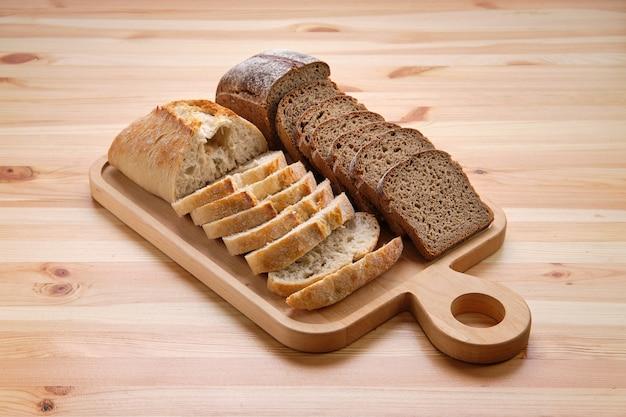 Biały i brązowy chleb na drewnianej desce do krojenia Premium Zdjęcia