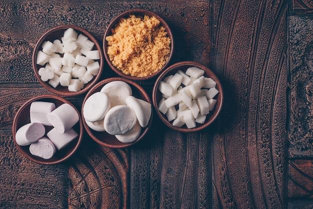 Biały I Brązowy Cukier W Miskach Z Cukierkami I Pianki Z Góry Widok Na Ciemnym Drewnianym Stole Darmowe Zdjęcia