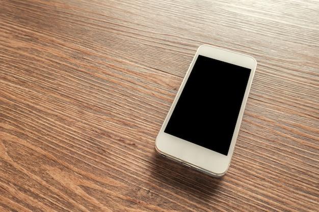 Biały inteligentny telefon z pustym ekranem na drewnianym biurku Darmowe Zdjęcia