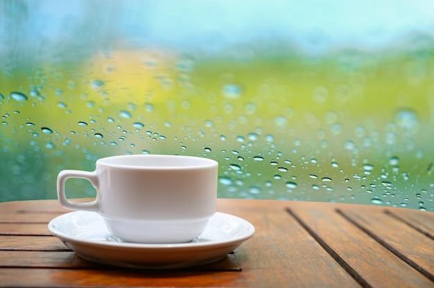 Biały kubek kawy umieszczony na drewnianym stole w naturalnym ogrodzie Premium Zdjęcia