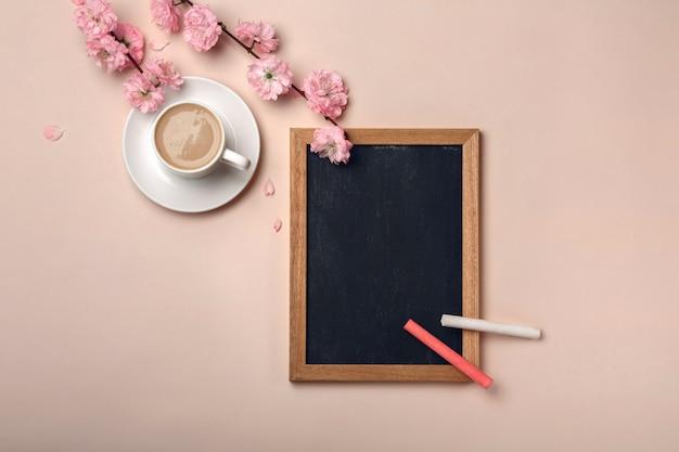 Biały kubek z cappuccino, kwiatami sakury, tablica kredowa na pastelowym różowym tle. Premium Zdjęcia