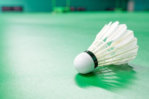Biały kurek wahadłowy do badmintona i cieniowanie neonu na zielonej podłodze Premium Zdjęcia