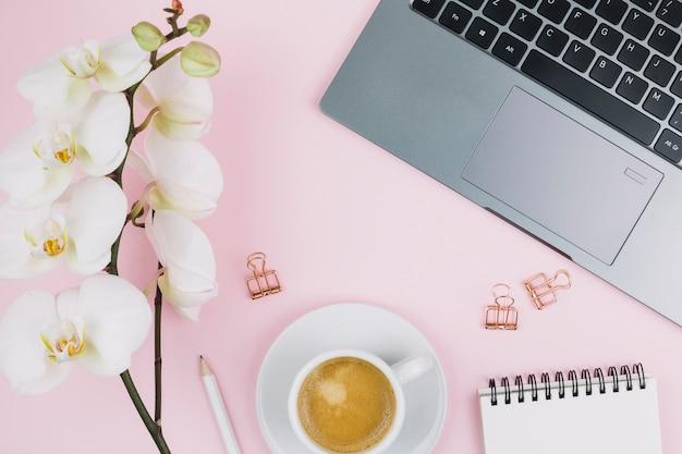 Biały kwiat orchidei; notes spiralny; ołówek; filiżanka kawy; laptop i spinacz do papieru na różowym tle Darmowe Zdjęcia