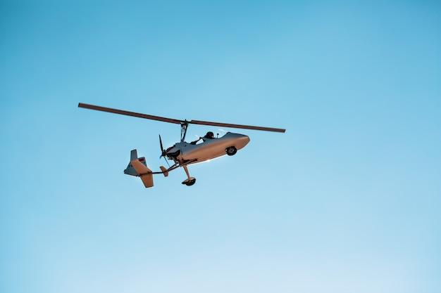 Biały mały podwójny wiatrakowiec autogyro bez kabiny na tle błękitnego nieba Premium Zdjęcia