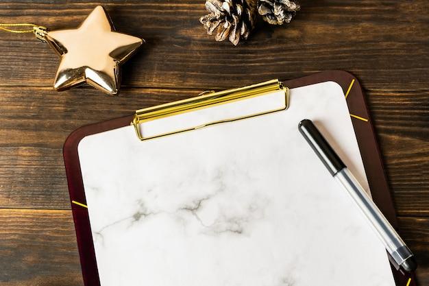 Biały marmurowy schowek i czarny długopis ze złotą gwiazdką Premium Zdjęcia