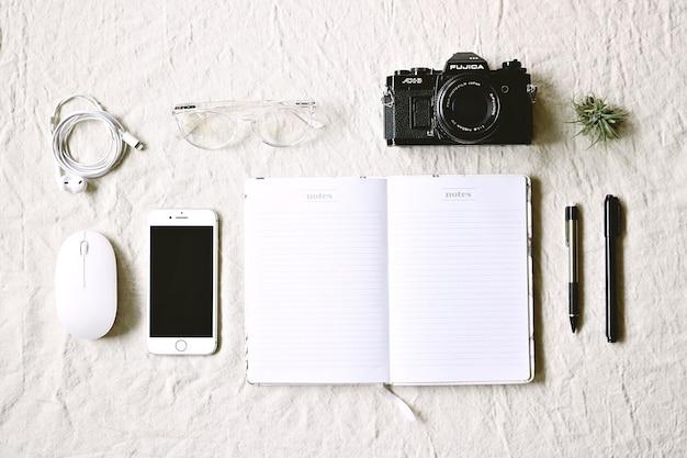 Biały Notatnik Obok Długopisów, Telefonu I Aparatu Darmowe Zdjęcia