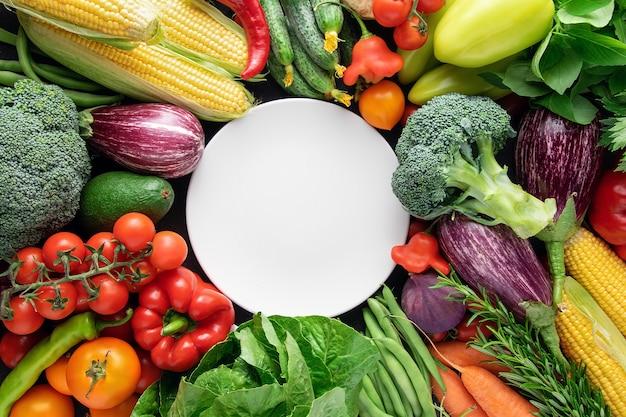 Biały Pusty Talerz Na Tle świeżych Organicznych Warzyw. Premium Zdjęcia