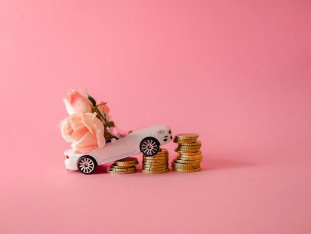 Biały samochód zabawka blisko monet dostarczających bukiet róż na różowym tle Premium Zdjęcia