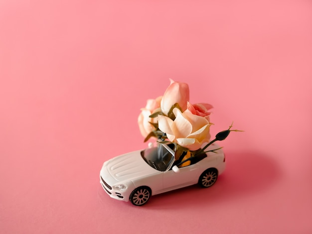 Biały samochód zabawka dostarczanie bukiet róż na różowym tle Premium Zdjęcia