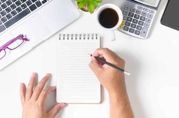 Biały Stół Biurka Z Ręką Człowieka Pisania Coś Na Pustym Notatniku Premium Zdjęcia
