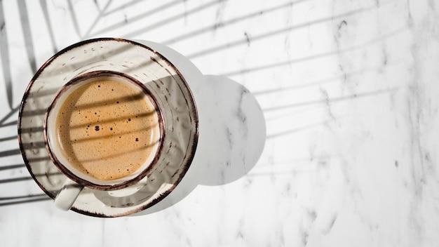 Biały wypełniony filiżanką kawy na białym tle objętym cieniem liścia fikusa Darmowe Zdjęcia