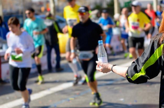 Bieg maratoński, biegacze na drodze, ochotnik podający wodę w punkcie gastronomicznym Premium Zdjęcia