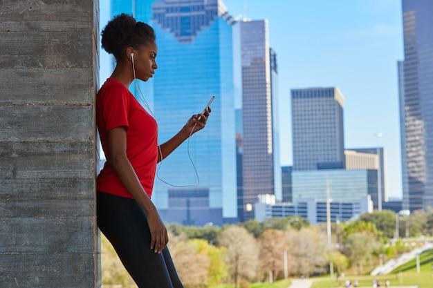 Biegacz Dziewczyna Słucha Muzyczne Słuchawki W Mieście Premium Zdjęcia