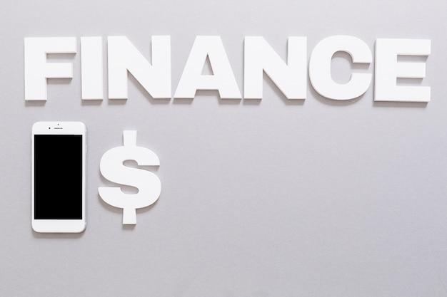 Bielu finanse słowo z dolarowym znakiem i smartphone na popielatym tle Darmowe Zdjęcia