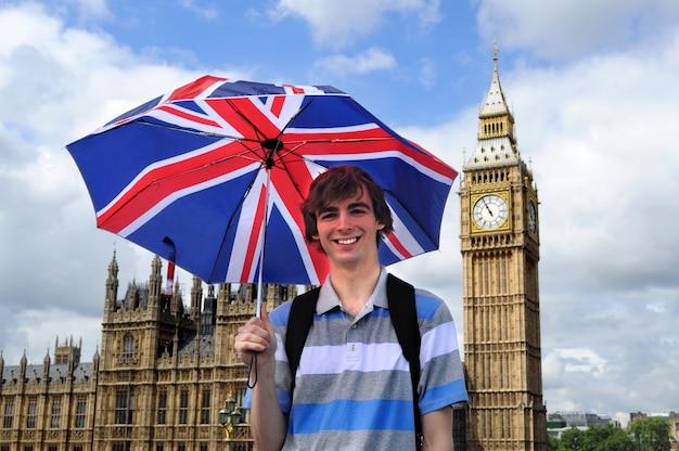 Big ben i turystyczny z brytyjskiej flagi parasolem w londynie Darmowe Zdjęcia