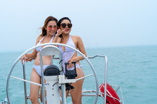 Bikini seksowna dziewczyna stoi i tańczy z kierownicą dłoni kierownicy na jachcie łodzi na tle morza i nieba Premium Zdjęcia