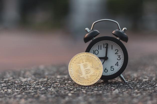 Bitcoin czarny budzik na kamiennej podłodze Premium Zdjęcia
