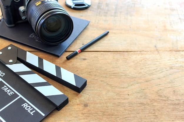 Biurko dyrektora filmowego. clapboard, książka i aparat cyfrowy na stole drewna Premium Zdjęcia