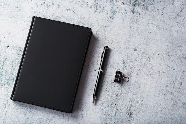 Biurko Z Czarnym Notesem I Długopisem Na Szarym Tle. Widok Z Góry Z Miejscem Na Kopię. Cele Biznesowe I Koncepcja Założeń Premium Zdjęcia