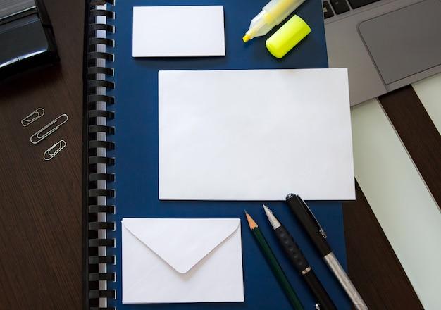 Biurko z uporządkowanym materiałem do pracy biurowej i pustymi kopertami i kartami do projektowania tekstu Premium Zdjęcia