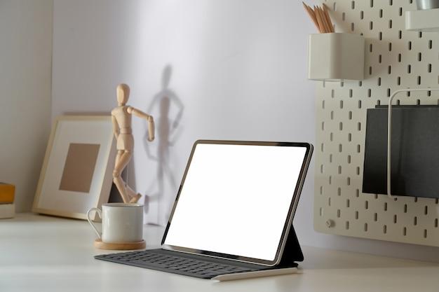 Biuro w domu biurko z pustego ekranu tabletu z inteligentną klawiaturą na minimalnym stole obszaru roboczego. Premium Zdjęcia